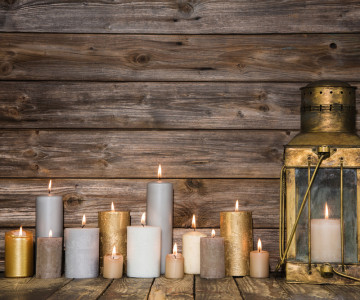 Wooden vintage background in with many burning candles and a old rustic lantern.