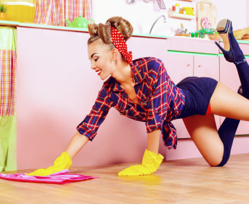 Pretty sexy pin-up girl cleans her glamorous pink kitchen. Retro style. Fashion.