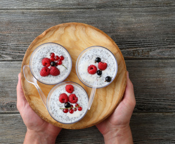 Chia seeds pudding with berries on plate, men's hands holding dish