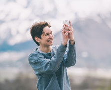 Young woman taking pictures on smartphone  in mountains. Tourism and leisure concept. Focus on hands