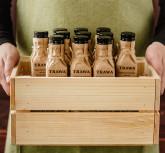 Постановочное фото бутылки масла в ящике TRAWA