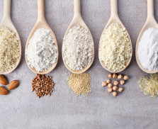 Wooden spoons of various gluten free flour (almond flour, amaranth seeds flour, buckwheat flour, rice flour, chick peas flour) from top view