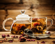 Teapot and glass cup with blooming tea flower inside against wooden background