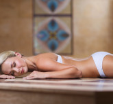 people, beauty, spa, healthy lifestyle and relaxation concept - beautiful young woman lying on hammam table in turkish bath