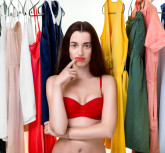 Young woman in underwear thinking what dress to wear in front of the clothes in wardrobe. Nothing to wear concept