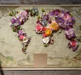 Map of world made from different kinds of flowers, on wooden background
