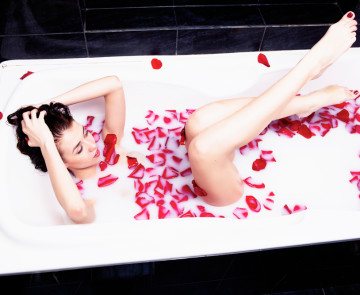 Girl in bath of milk with rose petals