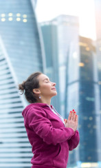 Young sporty model wearing pink sportswear practicing yoga near the skyscraper, namaste mudra pose, dreaming with her eyes closed, calm place for yourself in a big city, practicing healthy lifestyle